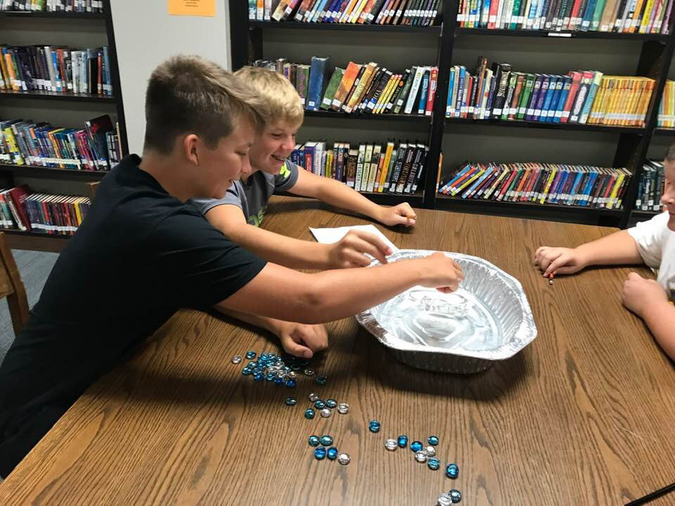 Students using marbles in experiment.