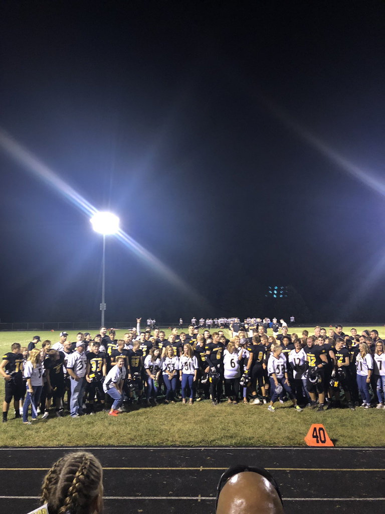 Football players and staff photo on field after game.