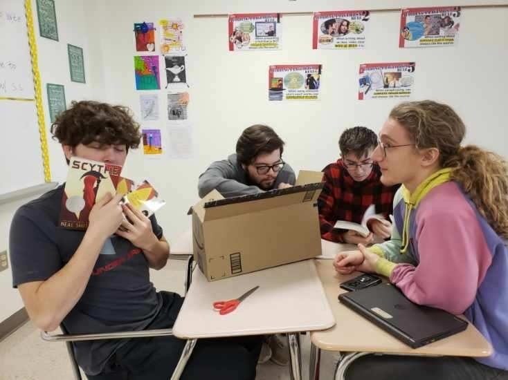 Students opening books from Donors Choose grant
